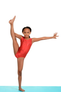 Black child doing gymnastics split with a white background
